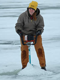 image of woman drilling hole on ice