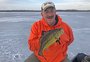 Image of Rick Hastings holding nice bass caught while ice fishing
