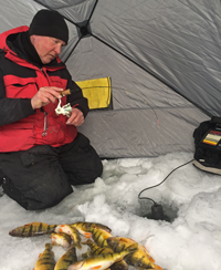 image of ice fisherman reeling up perch